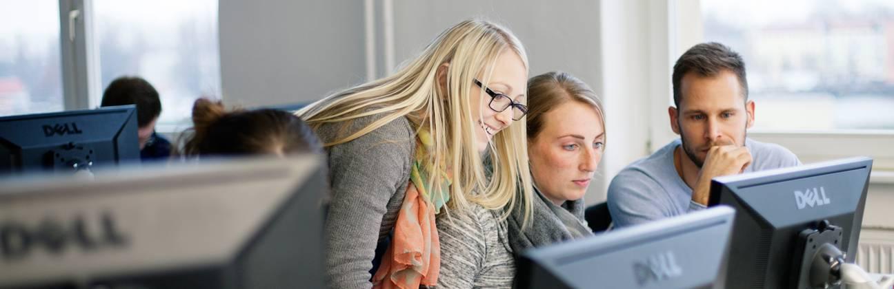 Drei Studierende vor Computern lernen