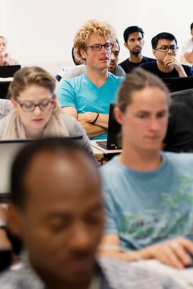 Studierende sitzen im Kursraum vor Computern