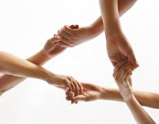 Sechs überkreuzte Hände zu einem Dreieck