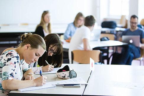 Zwei Studentinnen schreiben an einem Gruppentisch