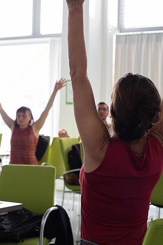 Dozentin und Studierende beim Schreibtischyoga