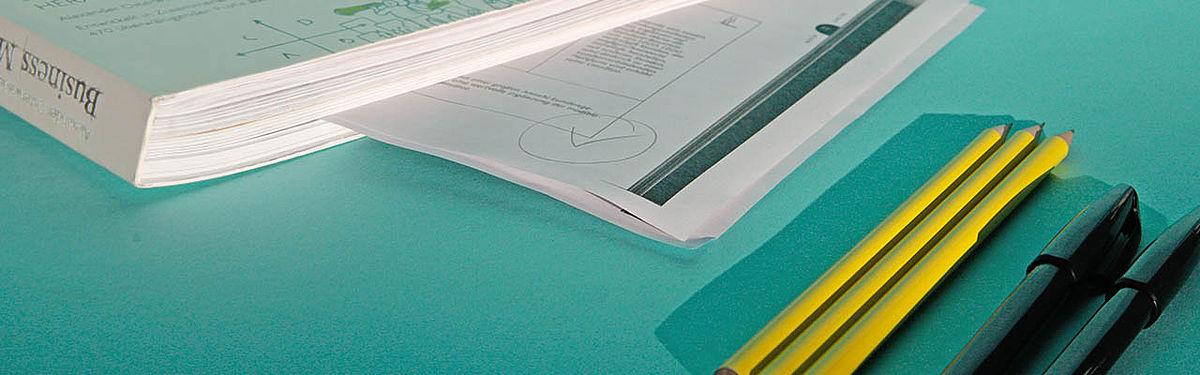 Mehrere beschriftete DinA4 Blätter auf türkisem Tisch, daneben 3 Bleistifte.