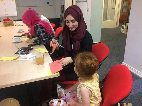 Internationale Studentinnen sitzen mit einem Kind am Tisch