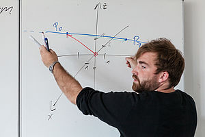 Tutor explains a mathematical formula on the whiteboard