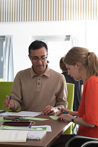 Eine Studentin und ein Student arbeiten zusammen am Tisch