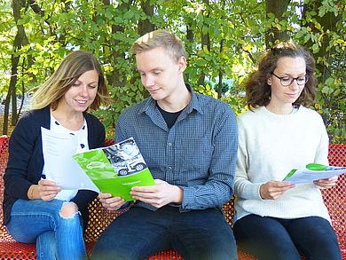 Drei Studierende mit Flyern auf einer Bank
