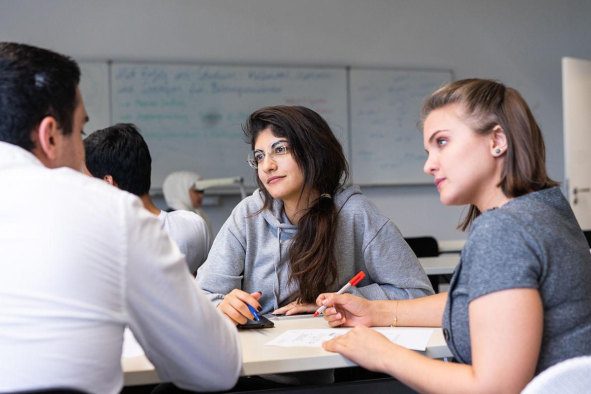 Kleine Gruppen von Studierenden lernen im Kursraum