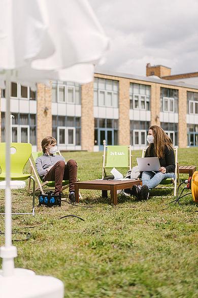 Zwei Studierende mit Mund-Nasen-Schutz sitzen mit Carpe-Campus-Equipment auf dem Campus Wilhelminenhof