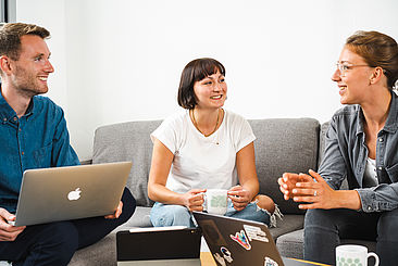 Studierende im Austausch mit Laptop