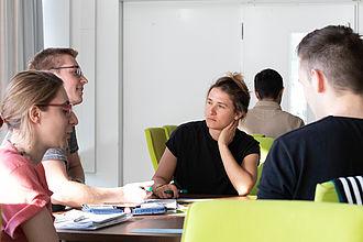 Kursteilnehmende im Gespräch am Gruppentisch