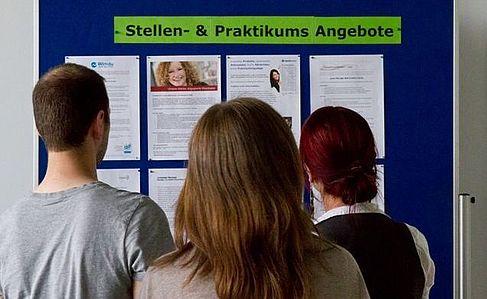 Drei Personen stehen vor der Stellen- & Praktikums-Infotafel