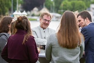 Ein Gruppe von Teilnehmenden unterhält sich im Freien mit Prof. Dr. Busch