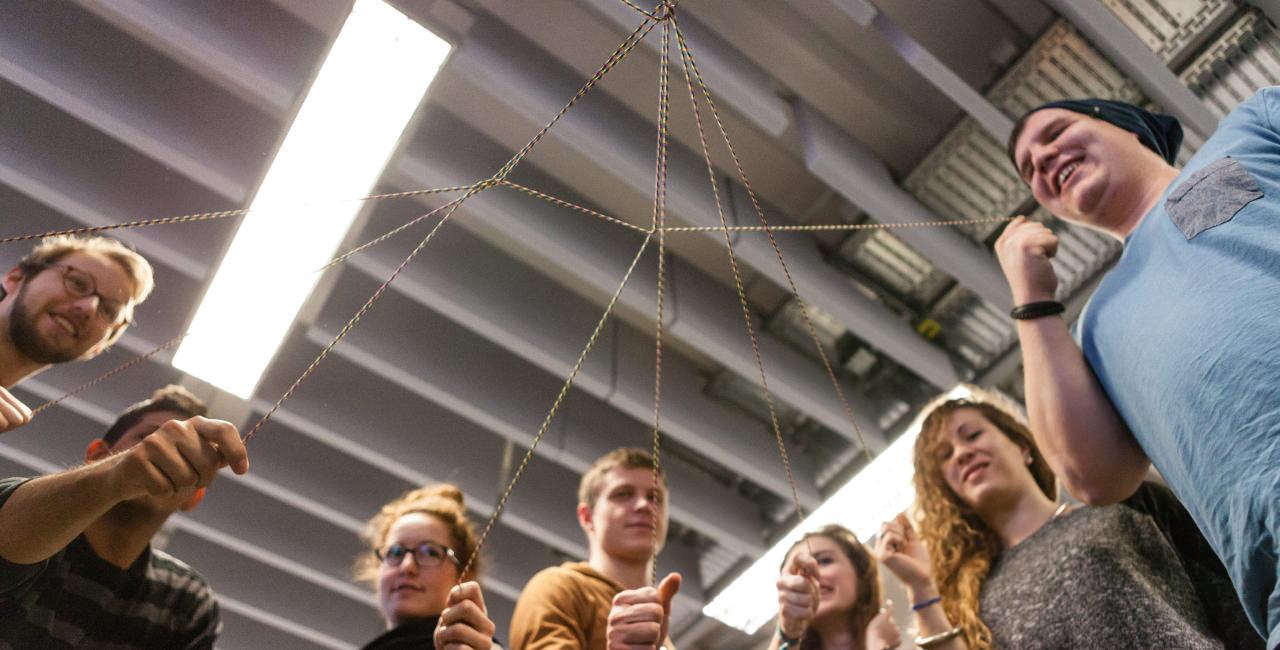 Junge Frauen und Männer halten einzelne Fäden eines Fadennetzes fest.