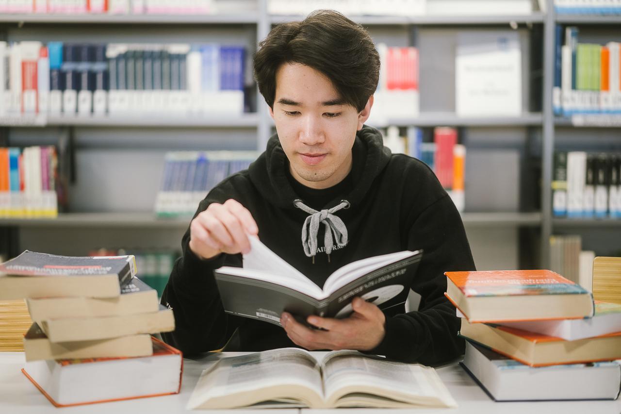 Student liest in der Bibliothek in einem Buch