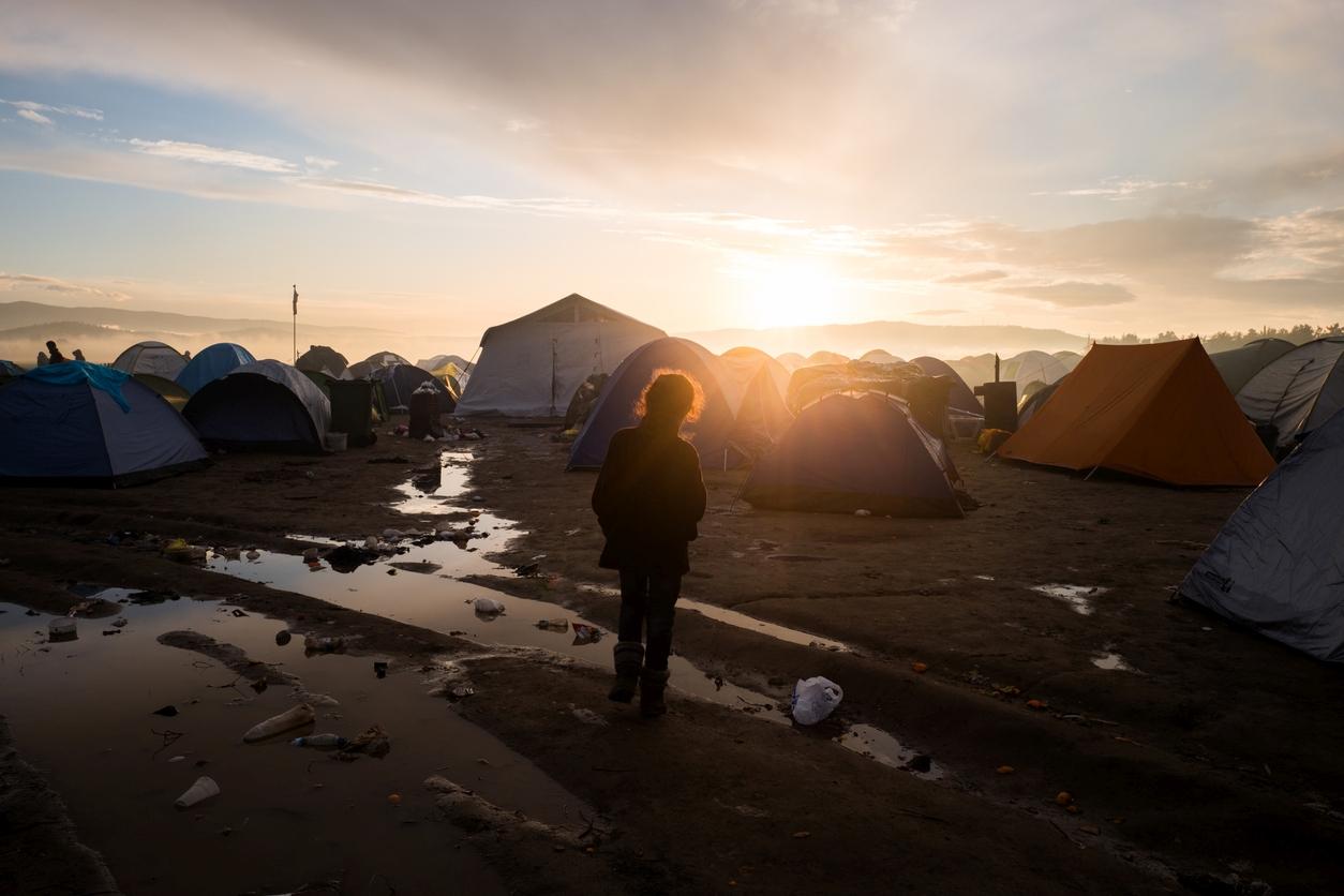 Geflüchtetes Kind, im Hintergrund ein Zeltlager vor einem Sonnenuntergang