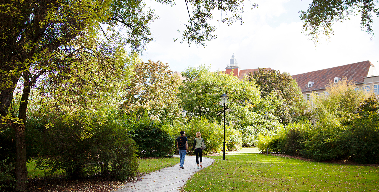 Two students walk along a path on the Campus Treskowallee