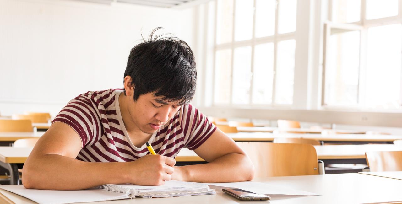Ein Student sitzt alleine im Kursraum und macht sich Notizen