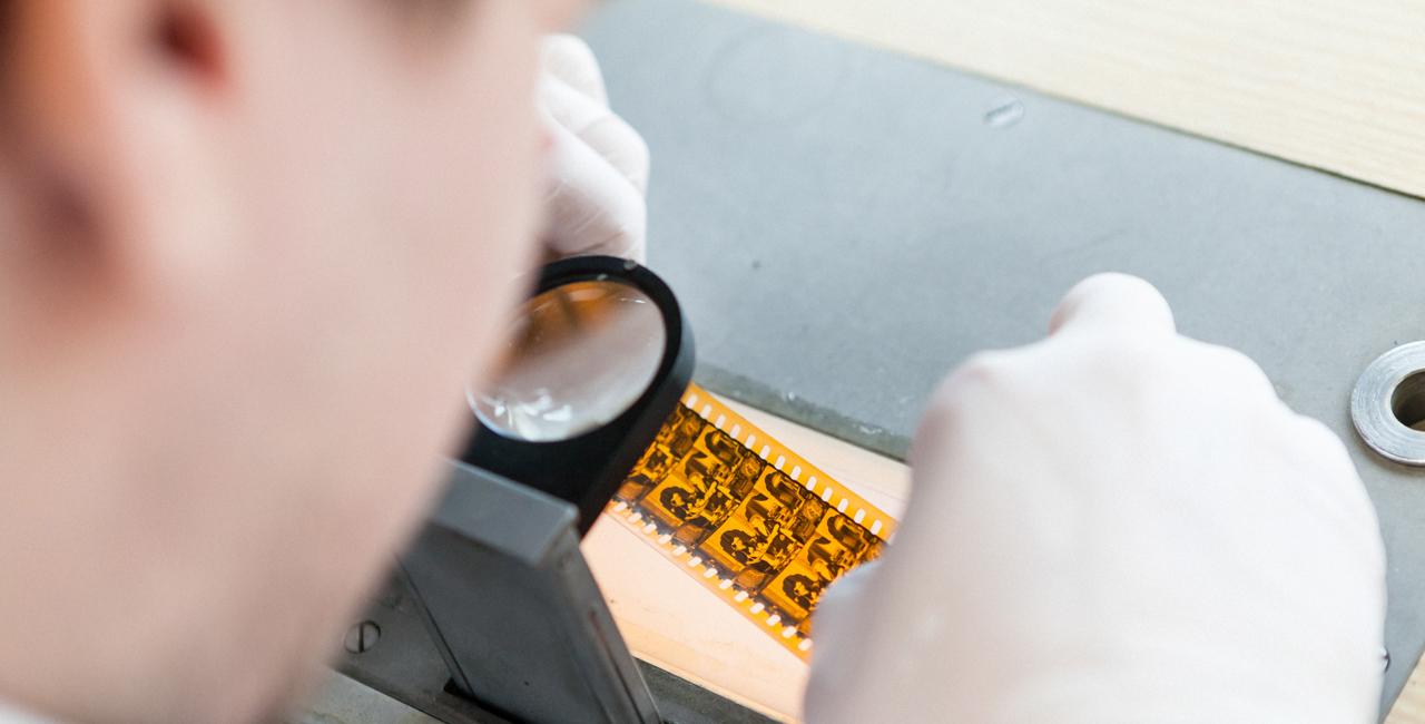 Ein Student legt einen Filmstreifen unter ein Vergrößerungsglas