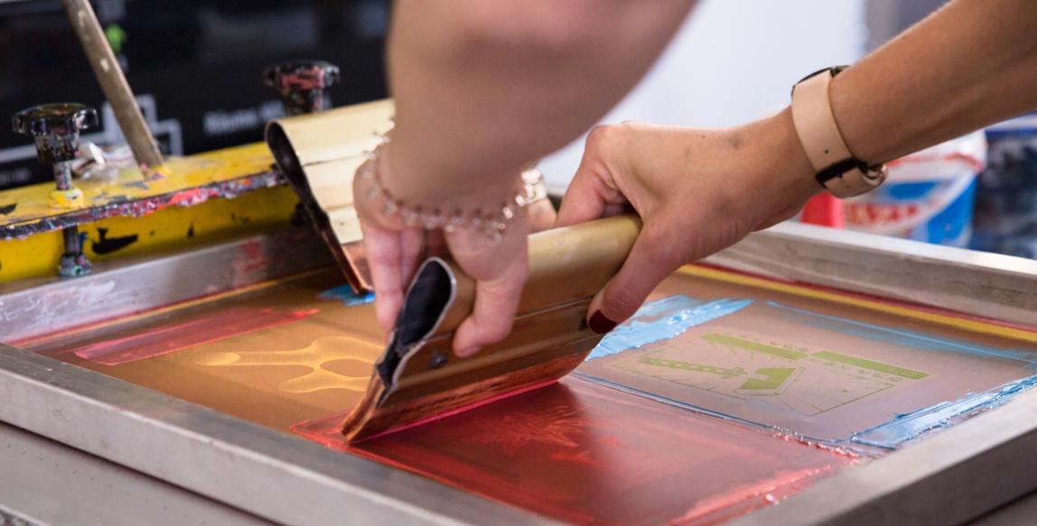 Eine Frau druckt 4 Bilder in einen Rahmen