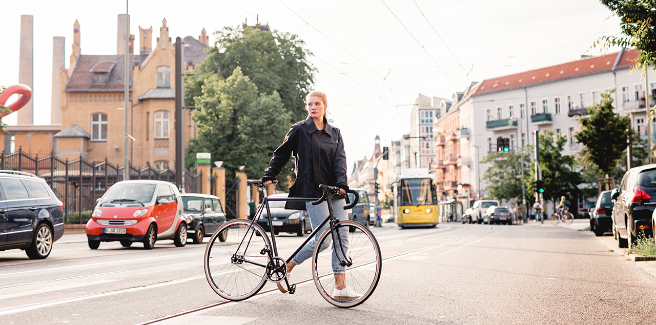 Studentin überquert mit Fahrrad eine Straße vor dem Campus Wilhelminenhof, im Hintergrund eine Straßenbahn