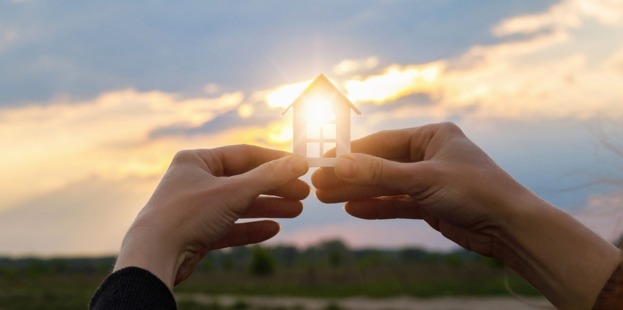 Hände halten ein Modellhaus gegen die Sonne