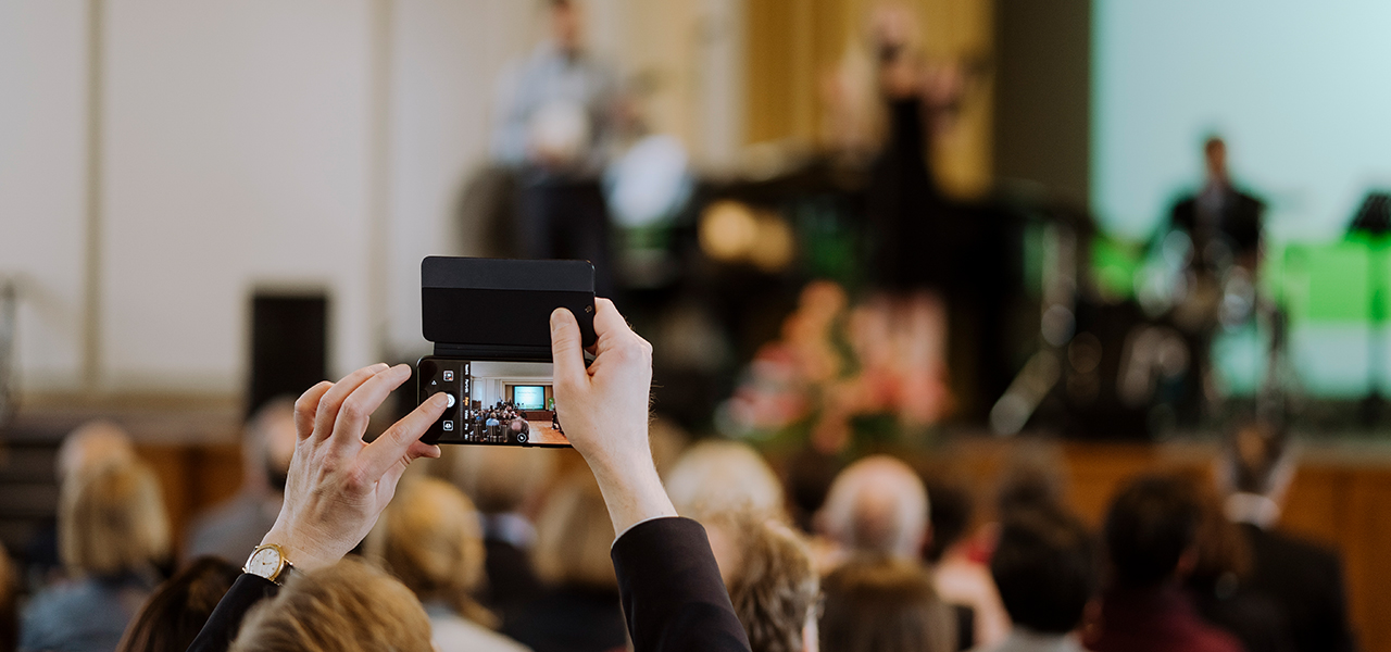 Veranstaltung im Audimax, jemand aus dem Publikum fotografiert die Bühne mit einem Smartphone