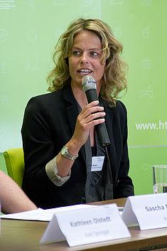 Unternehmensvertreterin auf dem Podium am Mikrofon
