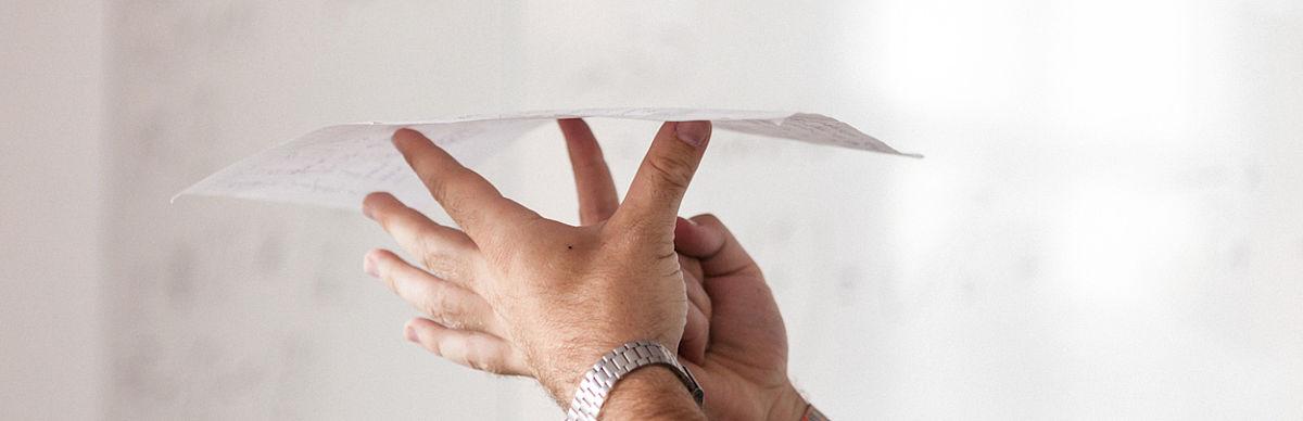 Ein Paar Hände balanciert ein Blatt Papier