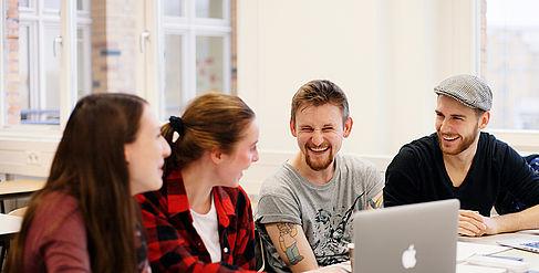 Studierende im Gespräch, vor ihnen ein Laptop