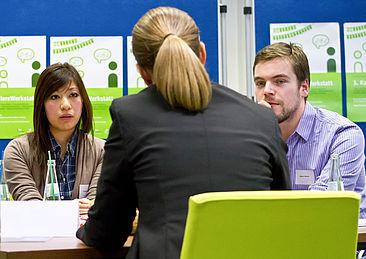 Zwei Studierende im Gespräch mit einer Unternehmensvertreterin