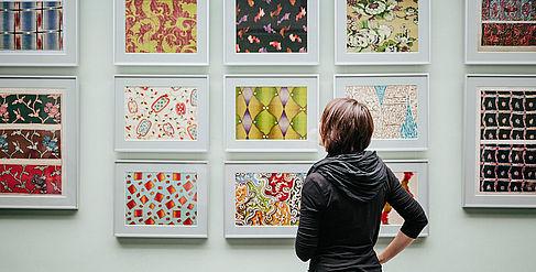 Studentin schaut auf Bilder an der Wand