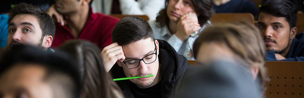 Student macht Notizen, einen grünen Bleistift im Mund