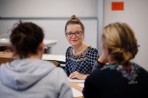Professorin im Gespräch mit zwei Studentinnen
