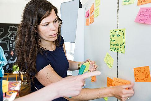 Mitarbeiterin pinnt einen Zettel an eine Wand