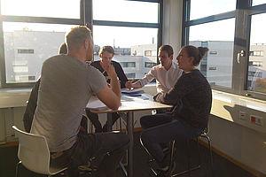 Gruppe von Gründer_innen bei einer Beratung