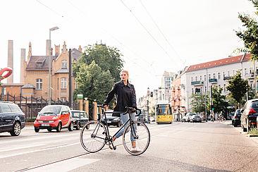 Studentin mit Rad vor dem Campus Wilhelminenhof