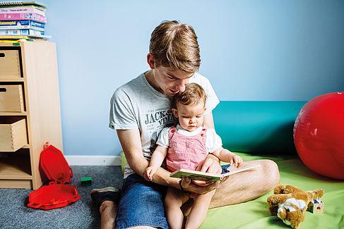 Vater liest seiner kleinen Tochter aus einem Buch vor