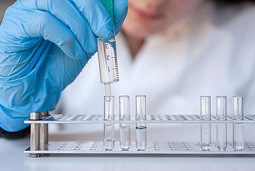 Mädchen tröpfelt eine durchsichtige Flüssigkeit in ein Reagenzglas