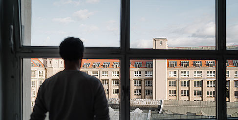 Student looks out the window at the Wilhelminenhof Campus