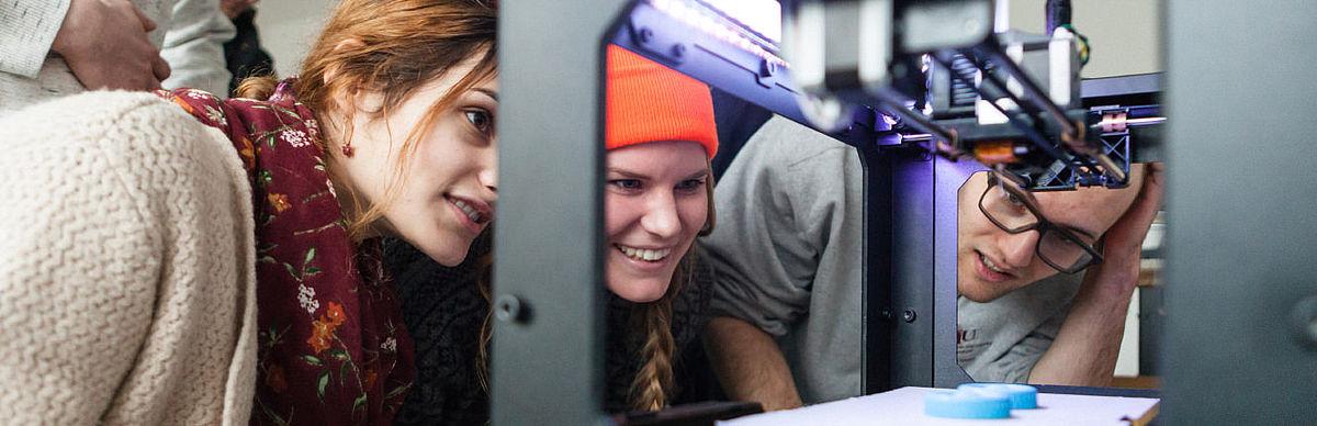 Drei Studierende am 3D-Drucker