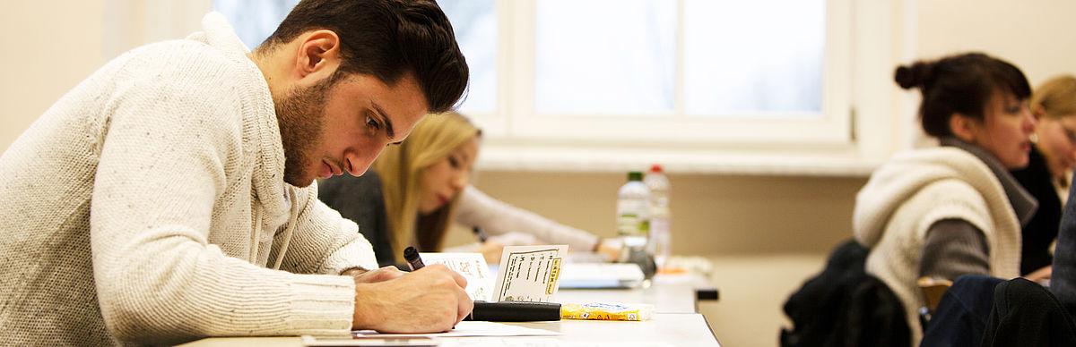 Schreibender Student in einer Lehrveranstaltung