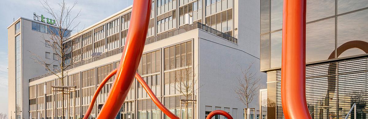 """Gebäude G auf dem Campus Wilhelminenhof, im Vordergrund Kunst am Bau mit dem Titel """"Leitung und Linie"""""""