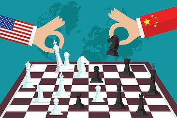 Arme, auf den Ärmeln die Flaggen der USA und von China, spielen Schach