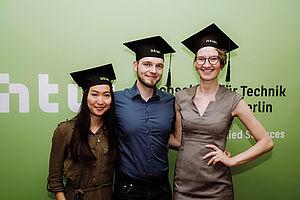 Drei Studierende bei ihrer Abschlussfeier