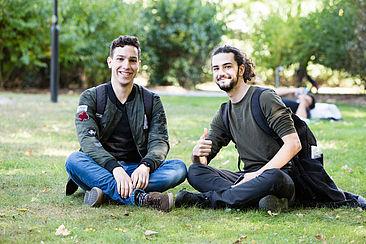 Zwei internationale Studenten sitzen auf der Wiese auf dem Campus Treskowallee