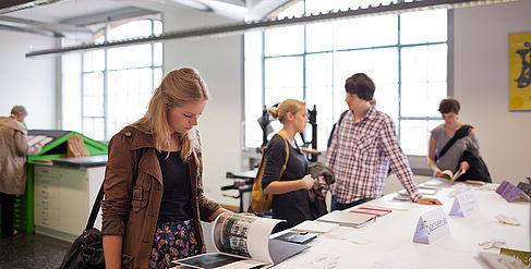 Besucherin blättert bei der Werkschau in einem Ausstellungsobjekt
