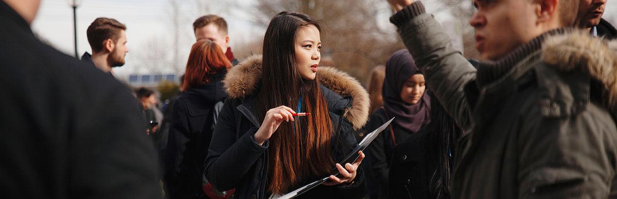 Studentin asiatischer Herkunft in einer Gruppe Studierender auf dem Campus Treskowallee