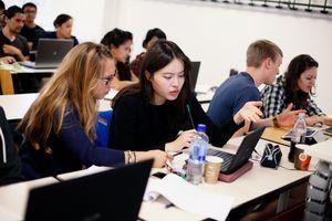 Zwei Studentinnen sitzen in einer Lehrveranstaltung am Laptop