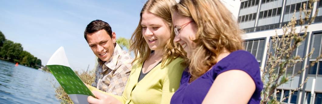Drei Studierende schauen in eine Broschüre