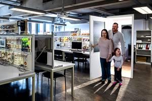 Plakativmotiv: Familie schaut überrascht von ihrer Wohnzimmertür in ein Labor